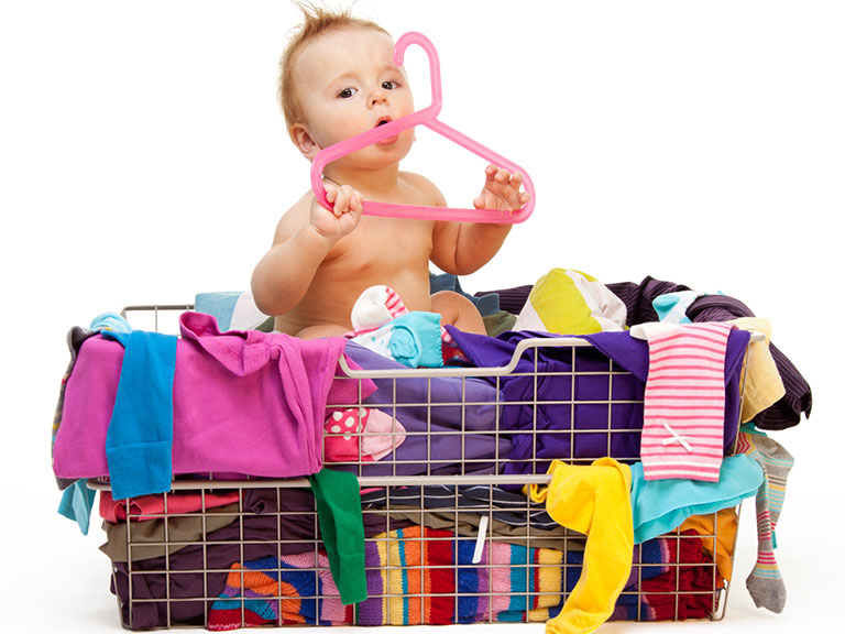 Baby sitting in laundry basket full of clothes holder a plastic hanger