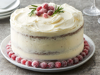 chocolate layer cake covered with vanilla frosting and sparkling sugared cranberries