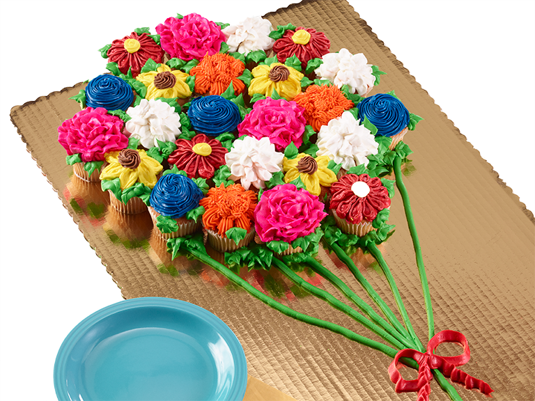 Frosted cupcakes made to look like flowers arranged together to form a balloon-like layout