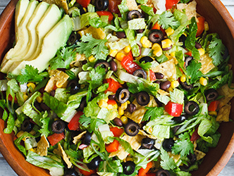 romaine lettuce salad with corn, black beans, tomatoes, peppers, olives, avocados, tortilla chips and dressing