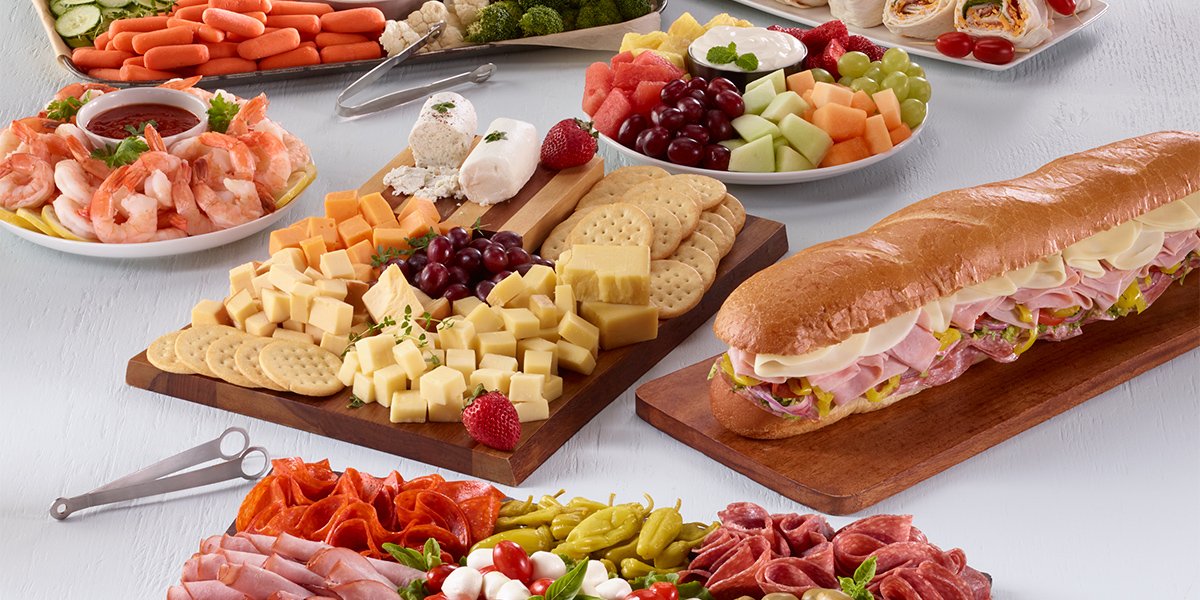 Array of party trays including meats, cheeses, vegetables, sandwiches and desserts