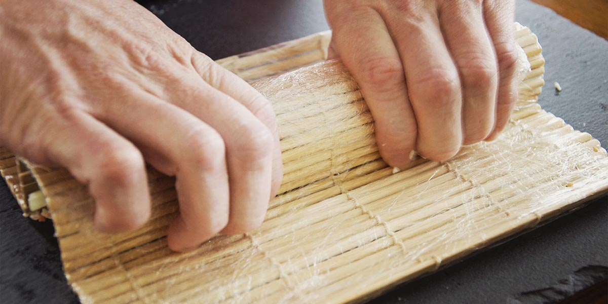 Finally a bamboo mat is used to evenly shape the roll in preparation for cutting.